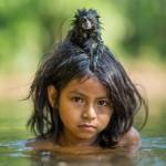 Тамарин на голове девочки из племени Мачигуенга, купающейся в реке Йомибато в национальном парке Ману, Перу.