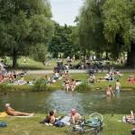 Любители позагорать в одежде и без неё на зелёных берегах ручья Швабингер-бах в Английском парке Мюнхена.