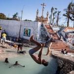 Дети плавают в реке, где рухнул мост, Порт-Салют, Гаити. Урагана Мэтью нанёс городу серьёзный ущерб, разрушив многие дома.